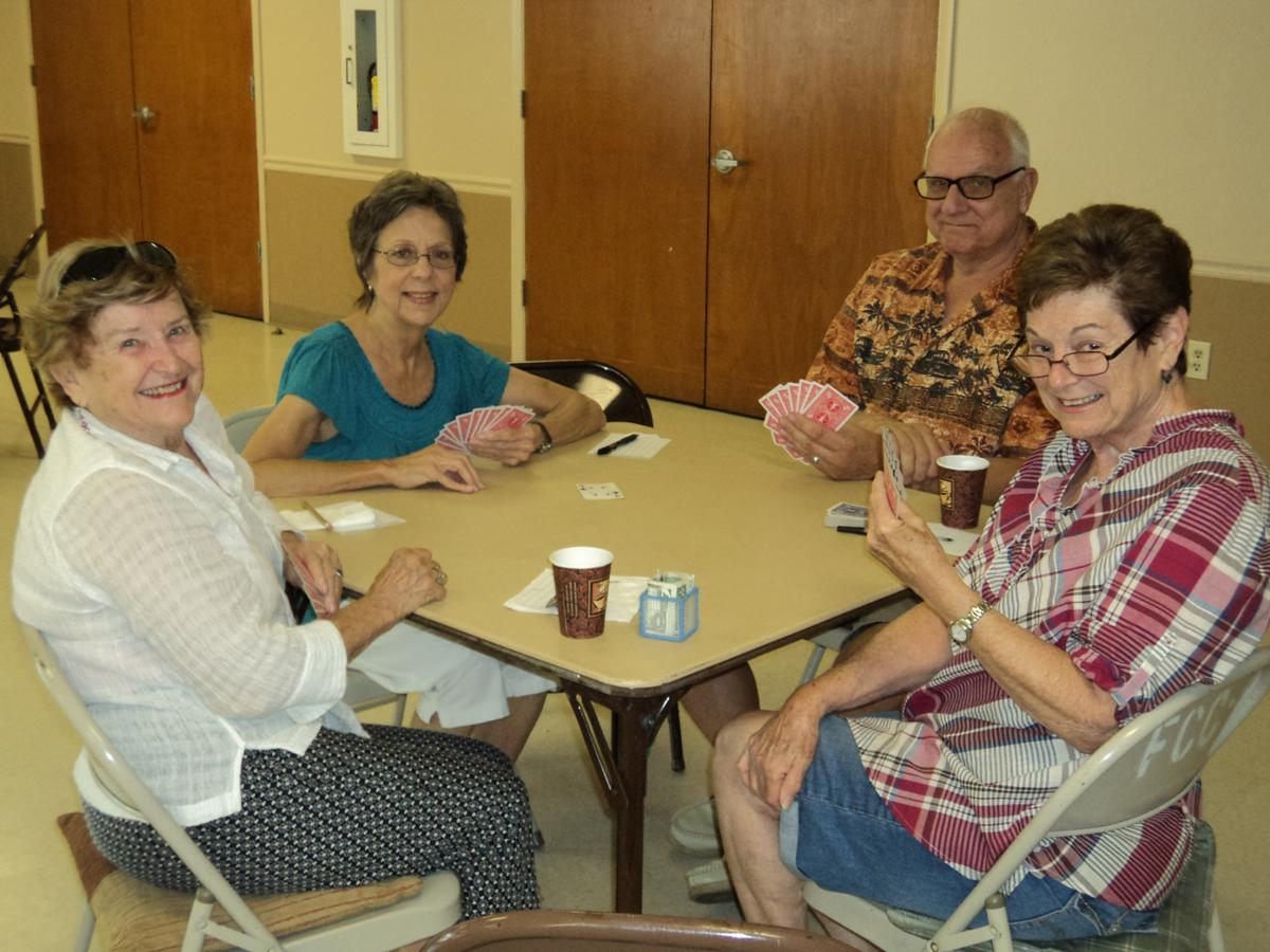 Group of senior citizens playing a card game.